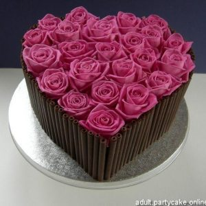 A brown base heart shaped cake with pink cream flowers as toppings