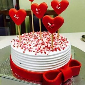 Beautifully decorated heart shaped cake with heart shaped red lolly pos on top