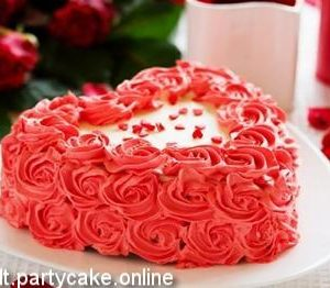 Heart shaped cake in red and white with decoration of red cream roses